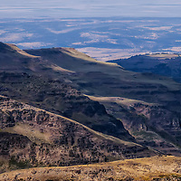 Another example of the overlaping ridges on Steens Mountain, outside of Frech Glen, Oregon. From these heights you can see forever, depending on how thick the haze or fog may be on any given day. This was in summer and there were wildfires in the area, which created the haze. Made for great photographic opotunities, however.