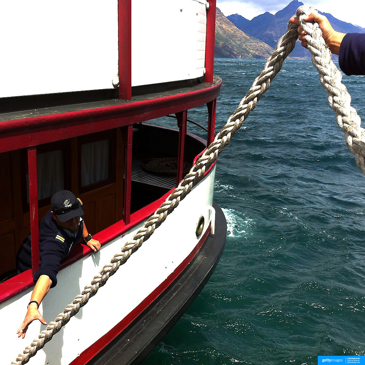 Crew members secure the berthing of the TSS Earnslaw, the 100 year old vintage coal fired passenger steam ship which sails on Lake Wakatipu, Queenstown, New Zealand. The popular tourist attraction is celebrating it's centenary year with celebrations planned for October 2012.  Queenstown, Central Otago, New Zealand. 29th February 2012. Photo Tim Clayton