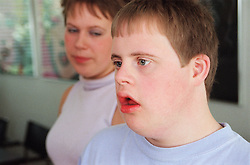 Teenage boy with Downs Syndrome standing next to sister,