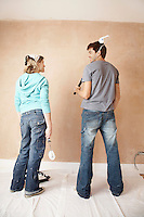 Couple standing holding paint rollers in unrenovated room back view