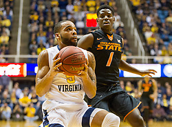 Jan 9, 2016; Morgantown, WV, USA; West Virginia Mountaineers guard Jaysean Paige (5) drives to the basket while being guarded by Oklahoma State Cowboys guard Jawun Evans (1) during the first half at the WVU Coliseum. Mandatory Credit: Ben Queen-USA TODAY Sports