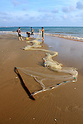 Four men gather up their fishing net on the beach. Mui Ne, Vietnam