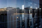London Bridge seen through corporate foyer window reflections.