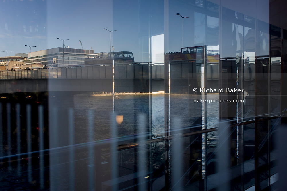 London Bridge seen through corporate foyer window reflections.
