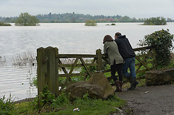 © London News Pictures. 01/05/2012. Tewkesbury, UK. A couple look over an expanse of flood water over farm land near the town of Tewkesbury, Gloucestershire, England on May 1, 2012. The UK has had its wettest April in over a century, with some areas seeing three times their usual average rainfall, according to figures from the Met Office. Photo credit : Ben Cawthra /LNP