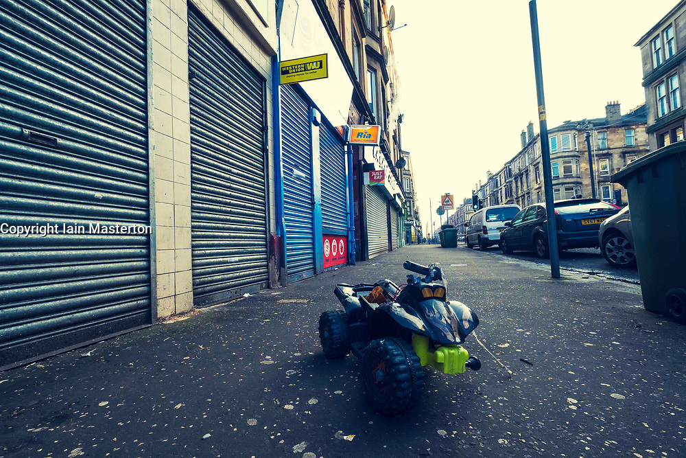 Abandoned child's toy and shuttered closed shops on street in Govanhill district of Glasgow, Scotland, United Kingdom