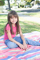 Young girl sitting on picnic blanket
