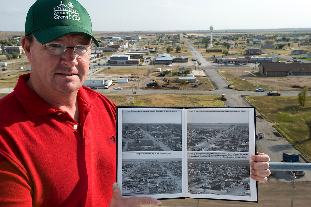 "Greensburg, Kansas, USA..The view on Greensburg from the grain silo, one of the few structures which survived the tornado. Matt Deighton shows a book called 'Blown Away' with pictures taken right after the tornado hit. Black and white images by Lane Allison...""Greensburg: Better, Stronger, Greener!"".On May 4, 2007, an EF5 tornado cut a 1.7-mile path of destruction through Greensburg, Kansas. Winds reaching speeds of 205 miles per hour uprooted trees, demolished homes and leveled the town. Eleven people died and 95% of the buildings were destroyed beyond repair. Residents have since worked furiously to rebuild it in a way that is both economically and environmentally sustainable and to meet the highest environmental standards. Greensburg, whose population has dropped from about 1400 to 800 following the storm and is now growing again, is currently the greenest town in America and the first in the United States to pass a resolution to certify that all city-owned buildings earn LEED Platinum accreditation, the highest level of the LEED rating system...Photo © Stefan Falke"