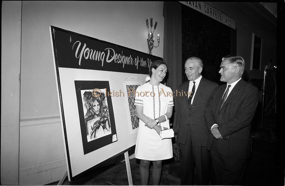 """28/06/1967<br /> 06/28/1967<br /> 28 June 1967<br /> Presentation of prizes at Navan Carpets """"Young Designer of the Year"""" reception in the Royal Hibernian Hotel, Dublin. Image shows Ms Linda Willis (20) a College of Art student from Dun Laoghaire, who was named Ireland's """"Young Designer of the Year"""". Linda, who was born in Venice, received her prize with the other award winners at the reception. Left -right are:  Ms Willis;  Mr. James White, Director National Gallery of Ireland and Mr. Allan Mallinson, Managing Director, Navan Carpets Ltd. standing in front of Linda's design."""