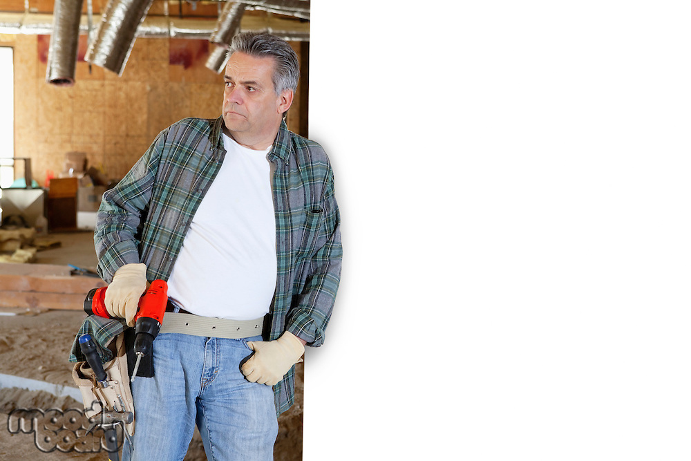 Construction worker holding drill while leaning on white wall