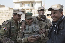 November 11, 2016 - Mosul, Nineveh, Iraq - 11/11/2016. Mosul, Iraq. Soldiers, belonging to the Iraqi Army's 9th Armoured Division, relax during a visit to Mosul's Hay Intisar district on the south east of the city. The district was taken by Iraqi Security Forces (ISF) around a week ago and, despite its proximity to ongoing fighting between ISF and ISIS militants, many residents still live in the settlement...The battle to retake Mosul, which fell June 2014, started on the 16th of October 2016 with Iraqi Security Forces eventually reaching the city on the 1st of November. Since then elements of the Iraq Army and Police have succeeded in pushing into the city and retaking several neighbourhoods allowing civilians living there to be evacuated - though many more remain trapped within Mosul. (Credit Image: © Matt Cetti-Roberts via ZUMA Wire)