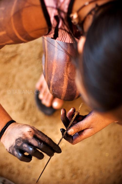 Kayapo woman preparing to paint their traditional tatoos with Genipapo ink.