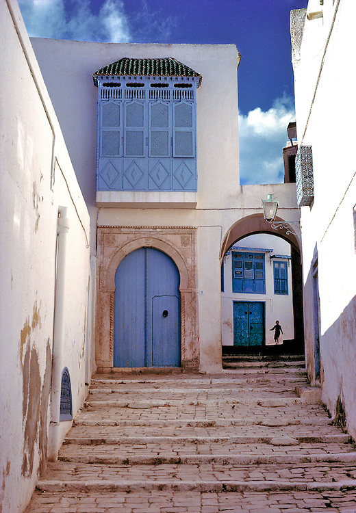 A lone figure silhouetted against the whitewashed walls of a small street in Sidi Bou Said, Tunisia, adds scale and interest to its architectural story.