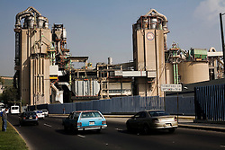 Cars drive by an Anagua Cement factory, on Tuesday, October 20, 2009, in Mexico City, Mexico. Anagua Cement is part of CEMEX.  Large companies provide some of the only tax base in Mexico.
