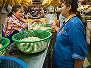 "11 AUGUST 2016 - BANGKOK, THAILAND:  A vendor (left) sells flower buds for garlands to customer in Pak Khlong Talat in Bangkok. Pak Khlong Talat (literally ""the market at the mouth of the canal"") is the best known flower market in Thailand. It is the largest flower market in Bangkok. Most of the shop owners in the market sell wholesale to florist shops in Bangkok or to vendors who sell flower garlands, lotus buds and other floral supplies at the entrances to temples throughout Bangkok. There is also a fruit and produce market which specializes in fresh vegetables and fruit on the site. It is one of Bangkok's busiest markets and has become a popular tourist attraction.      PHOTO BY JACK KURTZ"