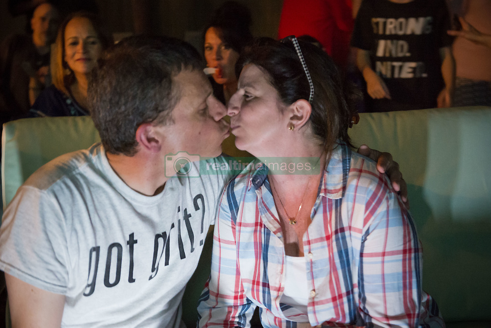 June 11, 2017 - Merrick, New York, United States - American Grit TV contestant CHRIS EDOM, 48, (wearing GOT GRIT? T-shirt), and his wife JOAN EDOM, both of Merrick, kiss each other as they host backyard Viewing Party for Season 2 premiere. Show. Edom family relatives and neighbors watched Episode 1 of FOX network reality television series  that Sunday night outdoors. has a military mentor. (Credit Image: © Ann Parry via ZUMA Wire)