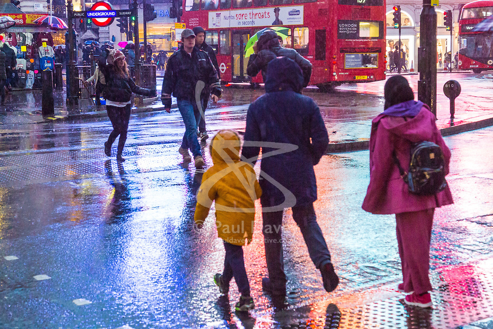 London, December 31 2017. The umbrellas come out as a downpour begins in London's west end ahead of the New Year's Eve fireworks at midnight. PICTURED: The light of the advertising hoardings is reflected in the wet road surface at Piccadilly Circus. © SWNS