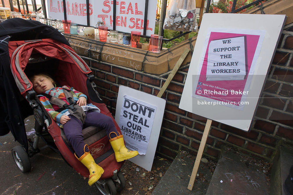 London, UK 2nd April: A young protester sleeps outside the now closed Carnegie Library, in Herne Hill, south London on 2nd April 2016. The angry local community in the south London borough have occupied their important resource for learning and social hub for the weekend. After a long campaign by locals, Lambeth have gone ahead and closed the library's doors for the last time because they say, cuts to their budget mean millions must be saved. A gym will replace the working library and while some of the 20,000 books on shelves will remain, no librarians will be present to administer it. London borough's budget cuts mean four of its 10 libraries will either close, move or be run by volunteers. ©Richard Baker / Alamy Live News.