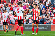 Luke O'Nien (#13) of Sunderland AFC celebrates with Alim Ozturk (#5) of Sunderland AFC at the final whistle of the EFL Sky Bet League 1 match between Sunderland and Portsmouth at the Stadium Of Light, Sunderland, England on 17 August 2019.