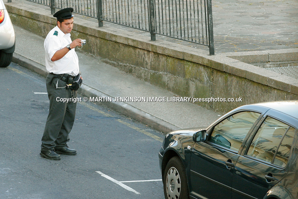 Traffic Warden photographs a car to provide evidence of the issuing of a parking ticket in Brighton ......