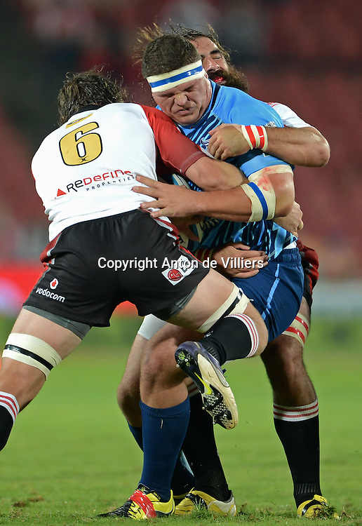 JOHANNESBURG, South Africa, 14 April 2012. Werner Kruger of the Bulls is tackled by Cobus Grobbelaar and Joshua Strauss (Capt) of the Lions during the Super15 Rugby match between the Lions and the Bulls at Coca-Cola Park in Johannesburg, South Africa on 14 April 2012. The Bulls won this away game 32-18.<br /> Photographer : Anton de Villiers / SASPA