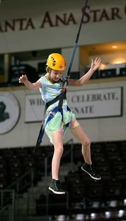 gbs031217h/RIO-WEST -- Amelia Willey, 10, of Rio Rancho, swings down from the Albuquerque Parks and Recreation's climbing wall during the New Mexico Firefighters Event for the St. Baldrick's Foundation which raises money for childhood cancer research at the Santa Ana Star Center on  Sunday, March 12, 2017. (Greg Sorber/Albuquerque Journal)