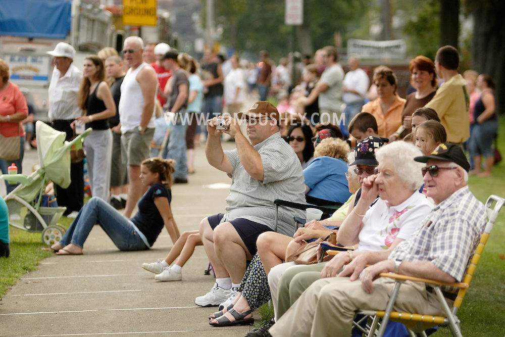 Middletown, N.Y. - Spectators, including a man taking photographs with a small digital camera, line Highland Avenue to watch the Middletown Fire Department's 147th Anniversary Fire Parade on Sept. 9, 2006. ©Tom Bushey