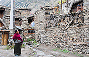 Woman walking Manang stone streets (Nepal)