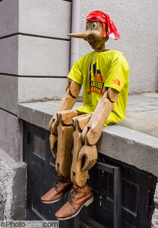 "A carved wooden puppet resembles Pinocchio, on the street of Cortina d'Ampezzo, in the Dolomites, Veneto, Italy, Europe. Pinocchio is a fictional main character of the children's novel ""The Adventures of Pinocchio"" (1883), by Italian writer Carlo Collodi. Carved by a woodcarver named Geppetto in a small Italian village, he was created as a wooden puppet, but dreamed of becoming a real boy. Pinocchio has a short nose that becomes longer when he is under stress (chapter 3), especially while lying."