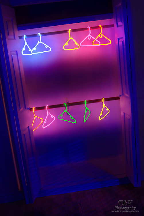 Glowing coat hanger in an empty closet.Black light