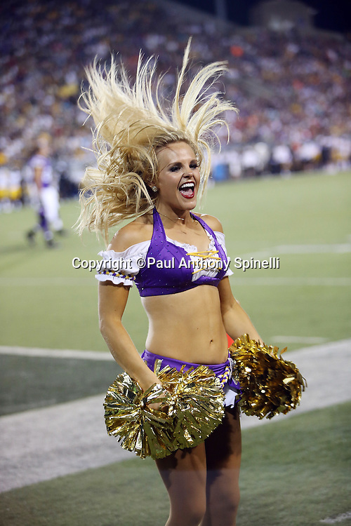 A Minnesota Vikings cheerleader flips her blonde hair as she cheers during the 2015 NFL Pro Football Hall of Fame preseason football game against the Pittsburgh Steelers on Sunday, Aug. 9, 2015 in Canton, Ohio. The Vikings won the game 14-3. (©Paul Anthony Spinelli)