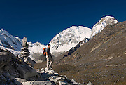 James Voortman beside a cairn, below the summits of Chopicalqui 6,354m (left), Huascarán Sur (South) 6,768m (centre) and Huascarán Norte (North) 6,664m (right).  Viewed from the trail between Pisco Base Camp and Laguna 69, at approx. 4,900m. Huascarán National Park, Cordillera Blanca, Peru.  Nikon D200, 17-50/2.8.