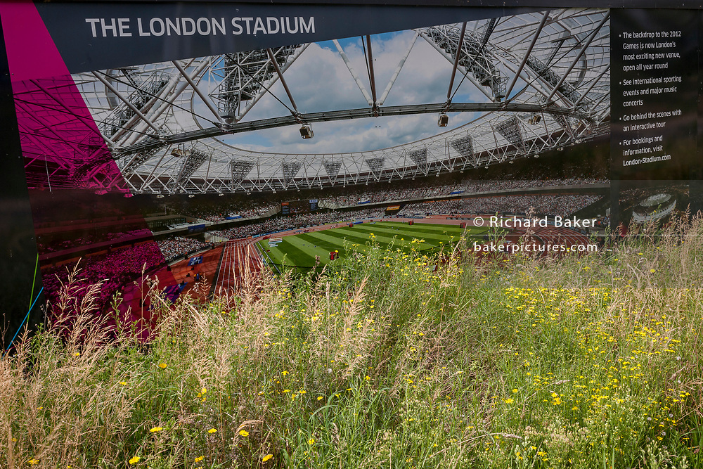 A construction hoarding featuring the London Stadium, once known as the Olympic stadium during the 2012 Olympiad, on 16th August 2017, in the Queen Elizabeth Olympic Park, Stratford, East London, England.
