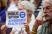 """Aug 26, 2009 -- PHOENIX, AZ: Supporters of the """"public option"""" hold up signs during Sen John McCain's town hall meeting on health care at North Phoenix Baptist Church in Phoenix, AZ, Wednesday. Sen McCain hosted his second town hall meeting on health care in two days Wednesday. About 1,000 people attended the meeting. Although most were opposed to President Obama's health care proposals and supported Sen McCain, there was a large group who support the President's health care efforts.  Photo by Jack Kurtz"""