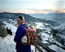A woman walks with her baby on her back in a traditional baby carrier on the ridge tat separates the village, in two, its early evening just after the sun has just set.