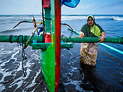 29 JULY 2017 - AIRKUNING, BALI, INDONESIA: A woman waits to pull her family's outrigger fishing canoe onto the beach after her husband spent a night at sea, fishing in the Indian Ocean, in Airkuning, a Muslim fishing village on the southwest corner of Bali. Villagers said their regular catch of fish has been diminishing for several years, and that are some mornings that they come back to shore with having caught any fish.    PHOTO BY JACK KURTZ