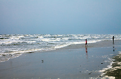 Child approaching incoming surf, with parent watching, at Spanish Grant development, West Beach, Galveston Island, Texas Gulf Coast.