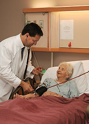 Doctor taking senior's blood pressure in hospice