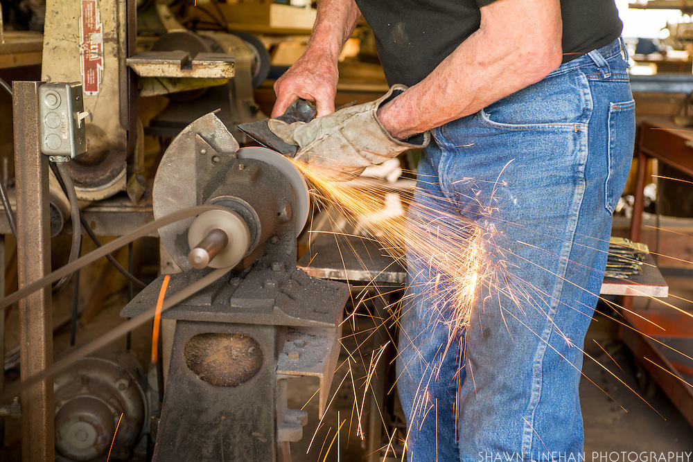 a metal garden tool being sharpened on a grinder.