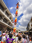"05 JULY 2014 - BANGKOK, THAILAND: An acrobat team forms a human pyramid on a side street in Bangkok during a parade for vassa. Vassa, called ""phansa"" in Thai, marks the beginning of the three months long Buddhist rains retreat when monks and novices stay in the temple for periods of intense meditation. Vassa officially starts July 11 but temples across Bangkok are holding events to mark the holiday all week.    PHOTO BY JACK KURTZ"