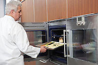 Mid- adult chef places baking tray in oven