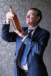 Bonhams whisky sale in Edinburgh on 7 June includes two salvaged bottles from the wreck of the SS Politician which were the inspiration for Compton MacKenzie's novel Whisky Galore. Also included in the sale is a 50 year-old Macallan Millennium Decanter distilled in January 1949.<br /> <br /> Pictured: Bonham's Whisky Consultant, Martin Green with Gilbey's - circa 1940 estimate &pound;6,000 - &pound;8,000.