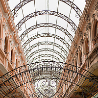 Ironwork archways and Victorian architecture in the covered shopping arcade in what was once the Casa de Correos y Telegrafos, or Central Post Office Building, in downtown Lima, Peru.