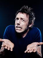 studio portrait on black background of a funny expressive caucasian man puckering interrogative hesitant