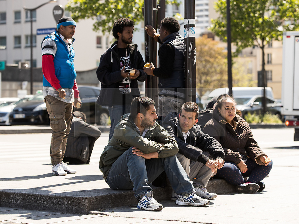 © Licensed to London News Pictures . 09/05/2017. Paris, France . People sit on the roadside at the scene where French police have cleared approximately 1000 people from an ad hoc roadside camp under roadways along a central reservation , in which migrants were living , in Porte de la Chapelle in North Paris , this morning (9th May 2017) . Photo credit: Joel Goodman/LNP