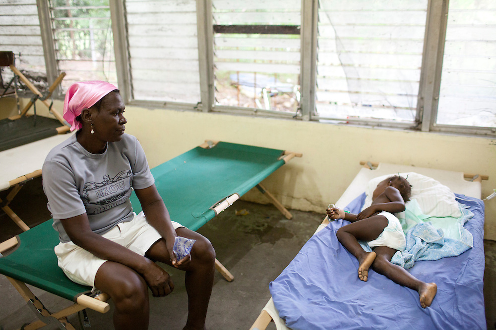 A woman watches over her young daughter, who is sick with cholera, at the Hospital Albert Schweitzer on Thursday, October 28, 2010 in Deschapelles, Haiti.