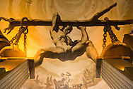 Manhattan, New York, U.S. - May 21, 2014 - At 30 Rockefeller Center 50th Street side entrance lobby, a vistor can see ceiling Mural by Spanish muralist Jose Maria Sert. It is one of four in lobby showing Man's Conquests. Sert used perspective to create optical illusion, so man astride the two columns in front of entrance door appears centered when viewer sees it from center of lobby, but man looks leaning to left when viewed from left side of lobby, and leaning to right when viewed from right side of lobby. Subjects proportionally bigger the closer to ceiling so viewers from floor level would view scene in proper perspective.