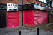 An empty shop unit which has a large estate agents To Let sign outside in Middlesborough town centre, North Yorkshire, United Kingdom.  The shop is secured with large red shutters to prevent entry.