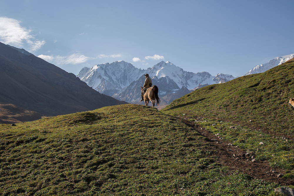 A cowboy rides towards Chok Tal over the rolling meadows created by the retreat of ancient glaciers at the foot of the mountain. The herdsman's livestock grazes here. Climate change in Kyrgyzstan is affecting cross border water rights in the already ethnically divided Fergana Valley, all while glaciers melt in the Tian Shan Mountains. Tensions are rising as different groups compete for scarcer and scarcer resources.