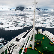 An ice-strengthened ship pushes through the sea ice at the northern end of the Lemaire Channel along the Antarctic Peninsula.